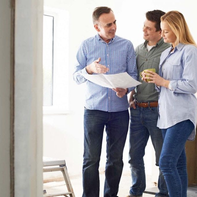 Couple Meeting With Architect Or Builder In Renovated Property